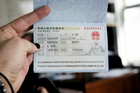 Hand holding up a passport open at the Chinese visa page