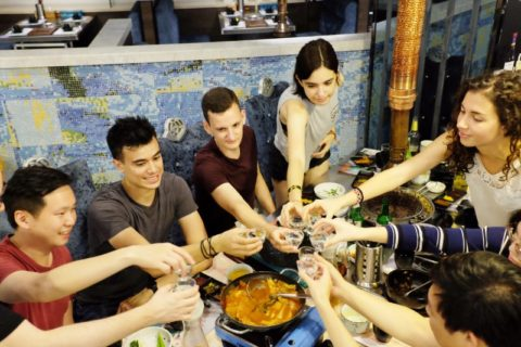 Large of group of people sitting around a table, toasting.