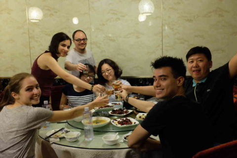 Group of LTL students and staff toasting at a dinner table
