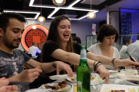 Excited students sitting at a dinner table
