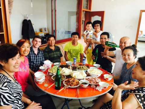 Homestay family, and student gathered around dinner table at home