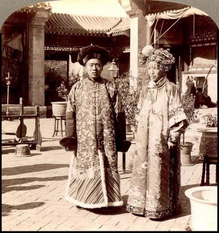 Bride and groom, wearing ornate Manchu wedding robes during Qing Dynasty. Notice the length, bagginess, and lack of a side split compared to a modern qipao.