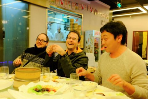 Three men sitting around a dinner table laughing